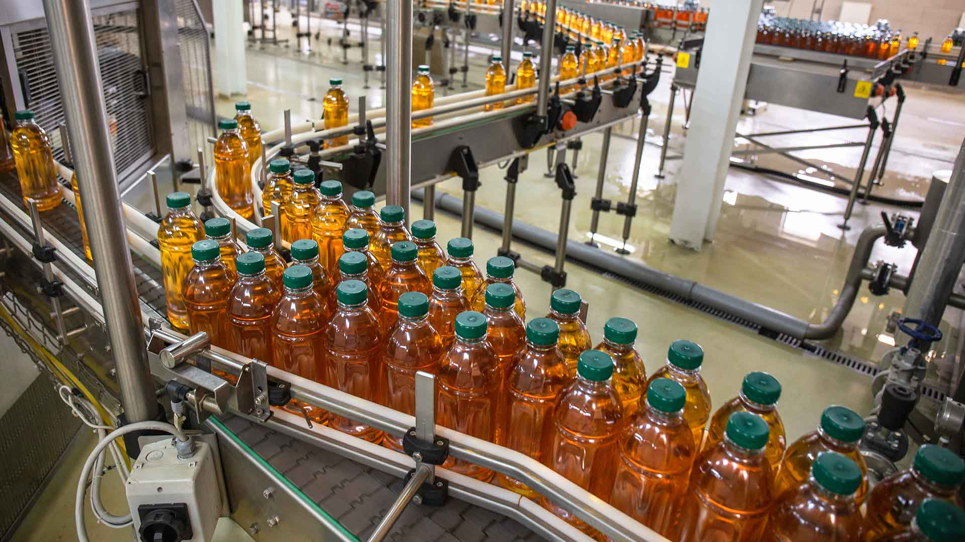 packaged, unlabeled apple juice on a production line