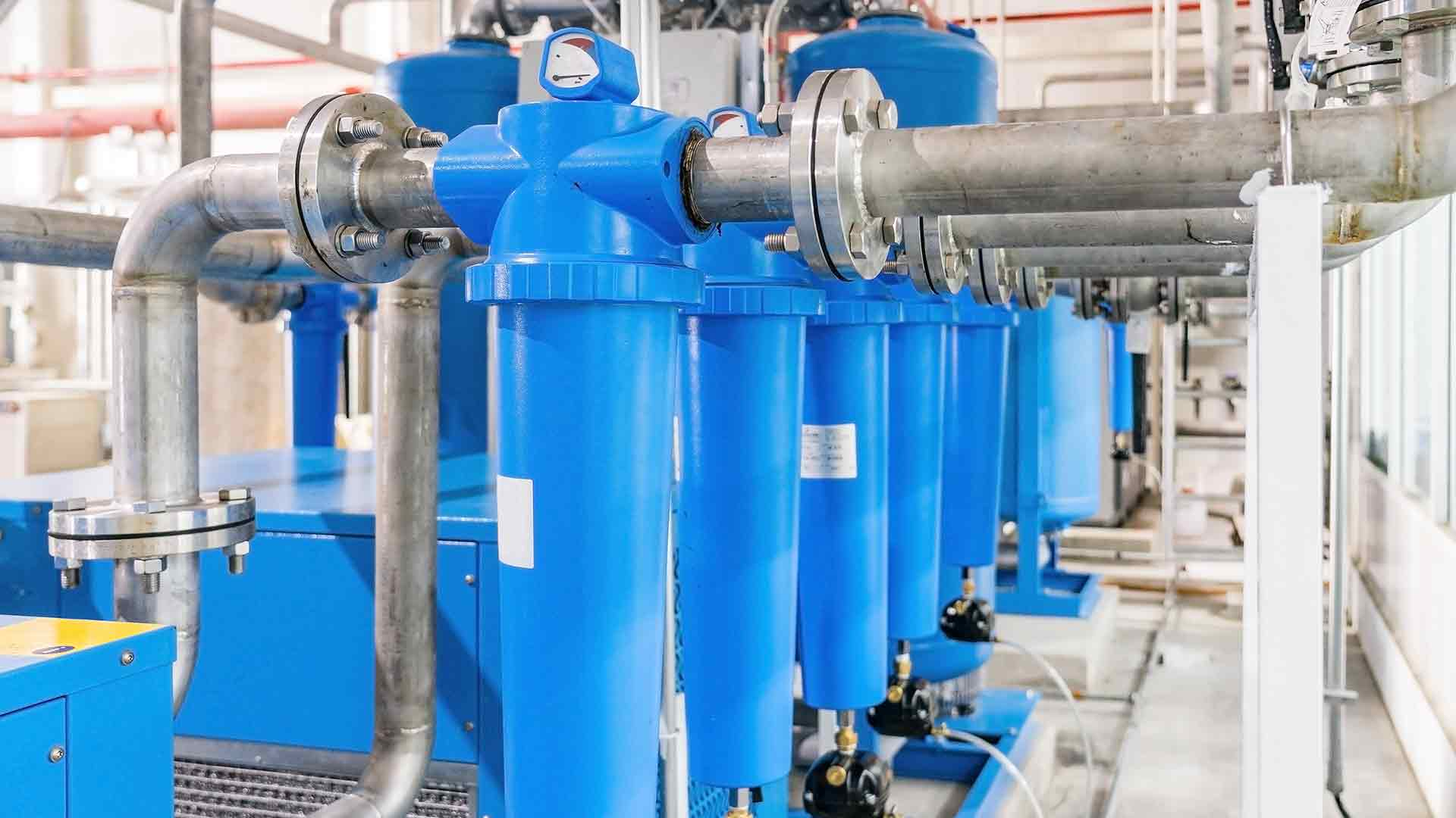 multiple blue compressed air dryers aligned in a large factory
