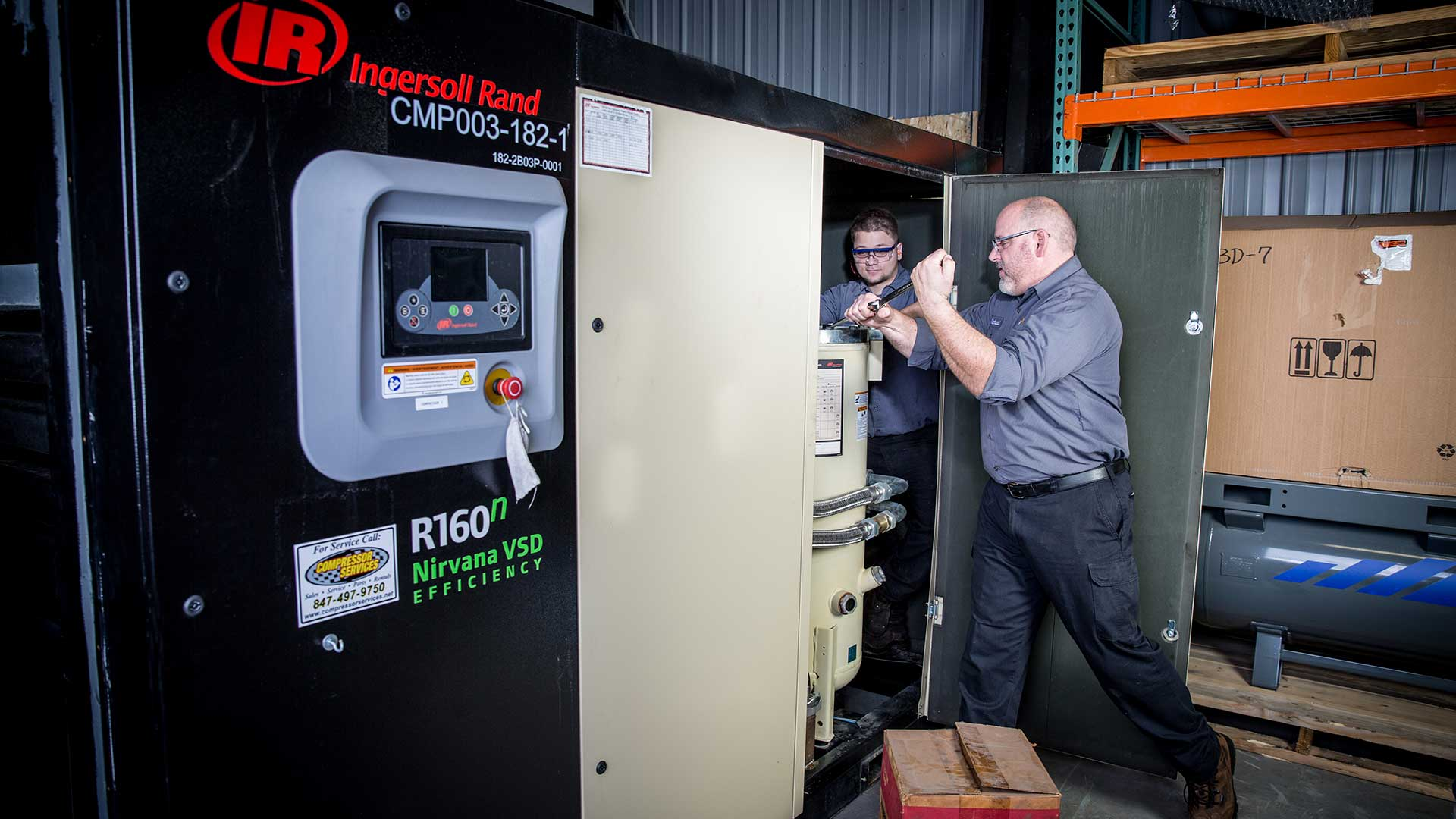 two compressor services employees performing preventative maintenance on an industrial air compressor